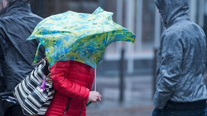 "A woman struggles against a gust of wind in Frankfurt, central Germany, Tuesday, March 31, 2015. Wide parts of Germany were hit by storm ""Niklas"". (AP Photo/dpa, Boris Roessler)"
