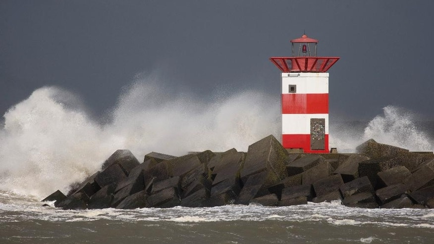 Waves batter against a lighthouse during stormy weather at the entrance to the port of Scheveningen, near The Hague, Netherlands, Tuesday, March 31, 2015. A storm with wind speeds of up to 110 kilometers (68 miles) per hour passed over The Netherlands and Germany. (AP Photo/Peter Dejong)