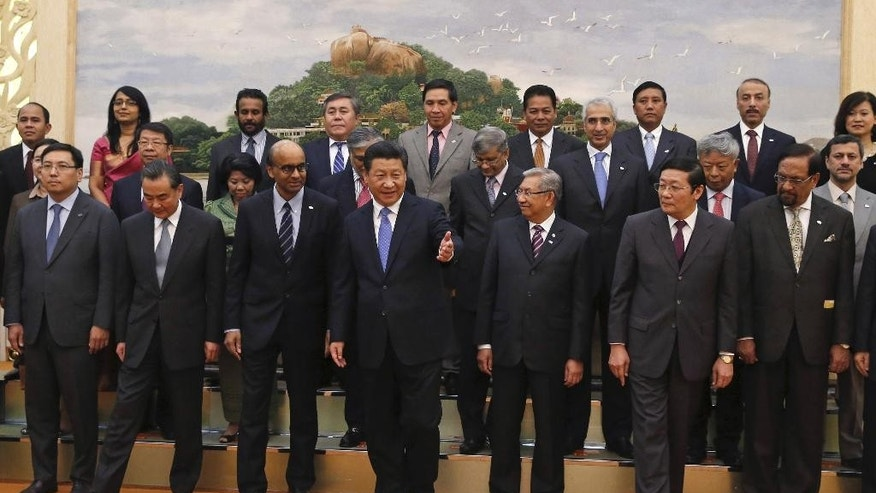 FILE - In this Friday, Oct. 24, 2014 file photo, Chinese President Xi Jinping, center, shows the way to the guests who attended the signing ceremony of the Asian Infrastructure Investment Bank at the Great Hall of the People in Beijing.  Japan has no plan as of now to join the China-led Asian Infrastructure Investment Bank, its government spokesman said Tuesday, March 31, 2015. (AP Photo/Takaki Yajima, Pool, File)