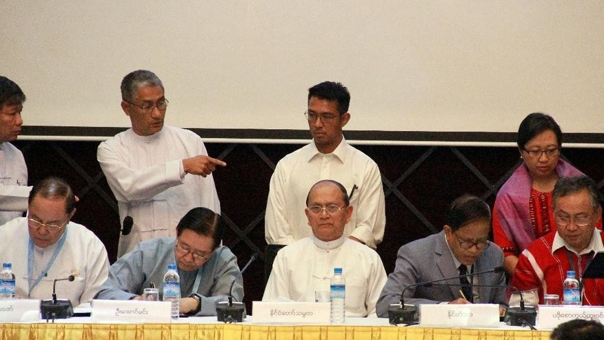 Myanmar President Thein Sein is seated at center while representatives of the government and armed ethnic groups sign an agreement on the draft of a nationwide cease-fire agreement, Tuesday, March 31, 2015, in Yangon, Myanmar. Myanmar's government and 16 ethnic armed groups agreed Tuesday on the wording of a draft nationwide cease-fire agreement aimed at ending decades of civil unrest. (AP Photo/Khin Maung Win)