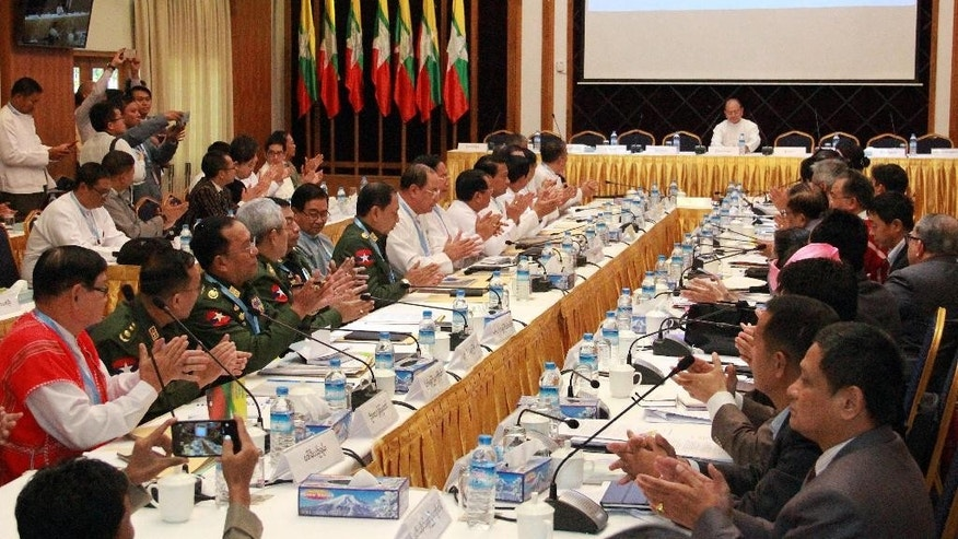 Representatives of Myanmar government and armed ethnic groups applaud as they listen to Myanmar President Thein Sein, top, speak during a signing ceremony agreeing on a draft cease-fire agreement, Tuesday, March.31, 2015, in Yangon, Myanmar. Myanmar's government and 16 ethnic armed groups agreed Tuesday on the wording of a draft nationwide cease-fire agreement aimed at ending decades of civil unrest. (AP Photo/Khin Maung Win)