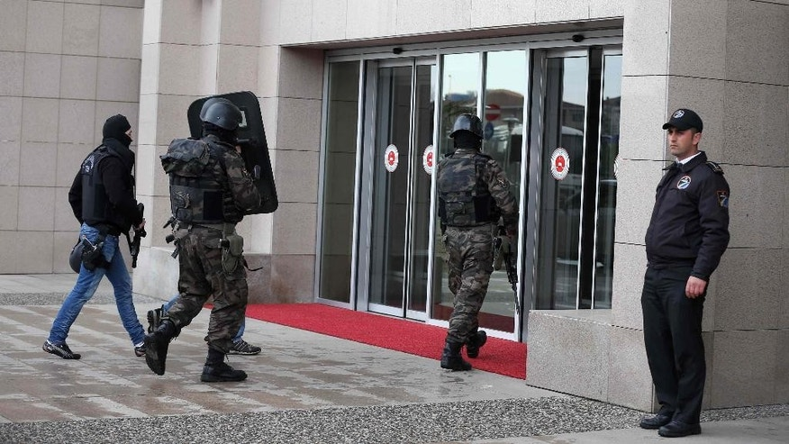 Members of special security forces enter  the main courthouse in Istanbul, Turkey, Tuesday, March 31, 2015. Turkish news agencies say that members of a banned leftist group have taken a chief prosecutor hostage in his office inside the courthouse. State-run Anadolu Agency and state television, TRT, identified the prosecutor as Mehmet Selim Kiraz. He is the prosecutor investigating the death of a teenager who was hit by a police gas canister fired during nationwide anti-government protests in 2013.(AP Photo/Emrah Gurel)