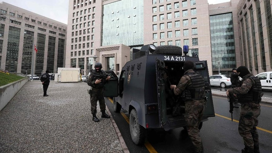 Members of special security forces stand outside the main courthouse in Istanbul, Turkey, Tuesday, March 31, 2015. Turkish news agencies say that members of a banned leftist group have taken a chief prosecutor hostage in his office inside the courthouse. State-run Anadolu Agency and state television, TRT, identified the prosecutor as Mehmet Selim Kiraz. He is the prosecutor investigating the death of a teenager who was hit by a police gas canister fired during nationwide anti-government protests in 2013.(AP Photo/Emrah Gurel)