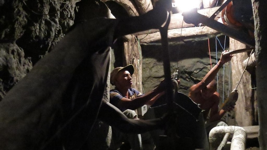 In this March 18, 2015 photo, miners work inside a mine for the blue-green gemstone known as larimar in Las Filipinas, Barahona province, Dominican Republic. The gem has provided a modest source of income for about 1,000 miners and their families since it was rediscovered four decades ago. (AP Photo/Ezequiel Abiu Lopez)