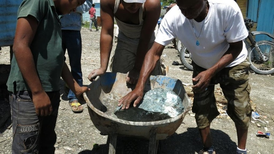 In this March 18, 2015 photo, miners look at a recently extracted larimar stone in Las Filipinas, Barahona province, Dominican Republic. The local mining cooperatives have held the right to dig since the early 1980s. They don't pay taxes and there are no official statistics about the economic impact of this growing informal industry. (AP Photo/Ezequiel Abiu Lopez)