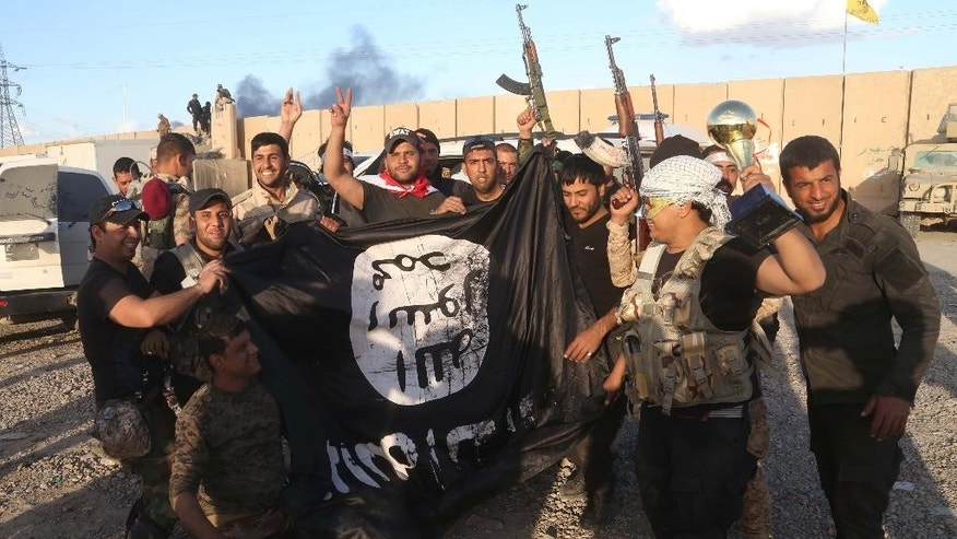 Iraqi security forces and allied Shiite militiamen celebrate as they hold a flag of the Islamic State group they captured in Tikrit, 80 miles (130 kilometers) north of Baghdad, Iraq, Tuesday, March 31, 2015. Iraqi forces battled Islamic State militants holed up in downtown Tikrit, going house to house Tuesday in search of snipers and booby traps, and the prime minister announced security forces had reached the city's center. (AP Photo/Khalid Mohammed)