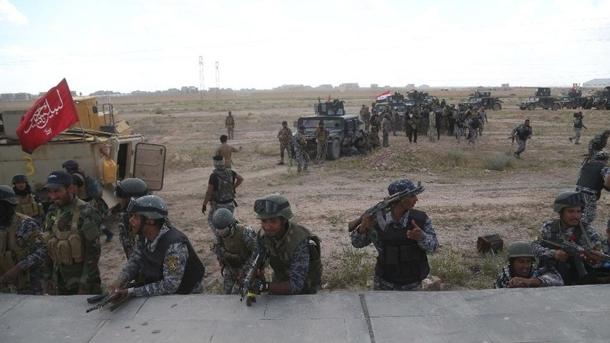 Iraqi security forces prepare to attack Islamic State extremists in Tikrit, 80 miles (130 kilometers) north of Baghdad, Iraq, Tuesday, March 31, 2015. Iraqi forces battled Islamic State militants holed up in downtown Tikrit, going house to house Tuesday in search of snipers and booby traps, and the prime minister announced security forces had reached the city's center. (AP Photo/Khalid Mohammed)