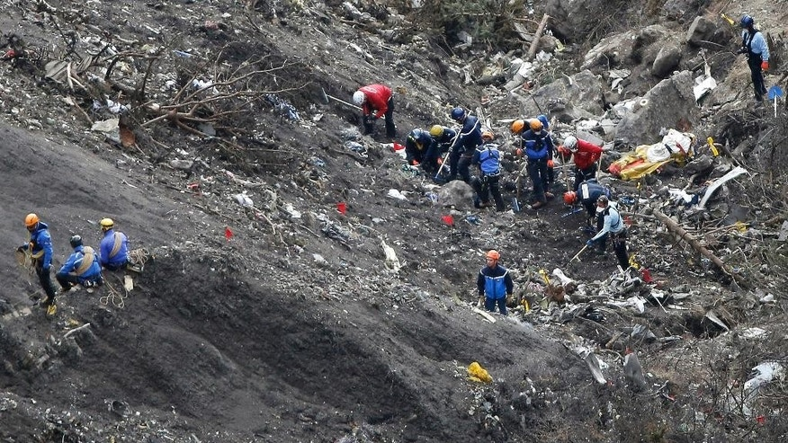 FILE - In this  Thursday, March 26, 2015 file photo, rescue workers work at debris of the Germanwings jet at the crash site near Seyne-les-Alpes, France. Investigators recovering remains from all 150 people aboard a German passenger jet that crashed into the Alps have accelerated their timeframe for identifying and matching their DNA _ whether that be from a body part or only a shred of skin. (AP Photo/Laurent Cipriani, File)