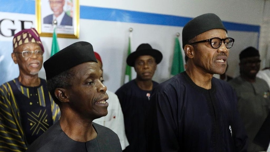 April 1, 2015: Nigerian former Gen. Muhammadu Buhari, right, along with his deputy Yemi Osibnajo sings the national anthem after speaking to journalists in Abuja, Nigeria.