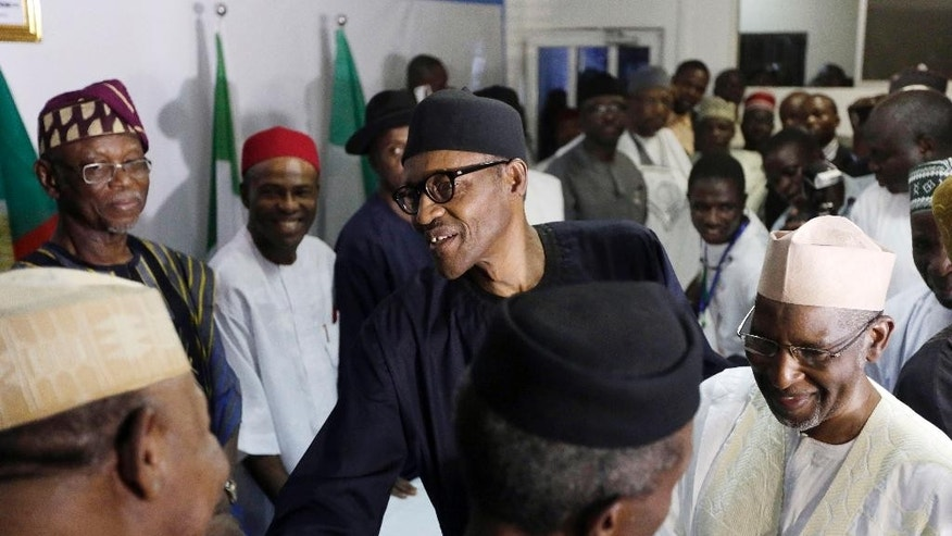 April 1, 2015: Nigerian former Gen. Muhammadu Buhari, center, shakes hands with party officials after speaking to journalists in Abuja, Nigeria.