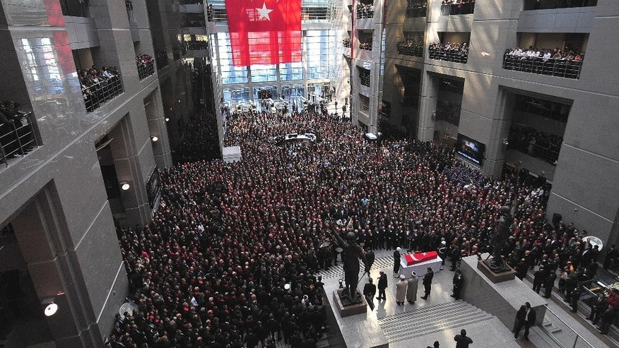Some thousands of people attend the funeral ceremony for Turkish prosecutor Mehmet Selim Kiraz inside the main courthouse where he died on Tuesday in Istanbul, Turkey, Wednesday, April 1, 2015. Istanbul's police chief, Selami Altinok said police had negotiated with the gunmen for six hours before the violent end of the hostage situation, resulting in the death of Kiraz and two gunmen who took him hostage. (AP Photo/Emrah Gurel)
