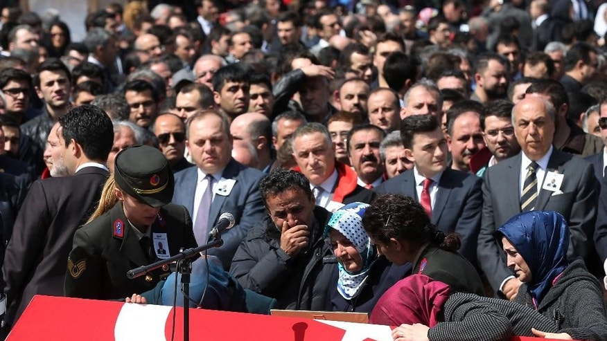 Family members, colleagues and politicians attend the funeral ceremony for Turkish prosecutor Mehmet Selim Kiraz, as many other people gather at the Eyup Mosque in Istanbul, Turkey, Wednesday, April 1, 2015. Istanbul's police chief, Selami Altinok said police had negotiated with the gunmen for six hours before the violent end of the hostage situation, resulting in the death of Kiraz and two gunmen who took him hostage. (AP Photo/Emrah Gurel)