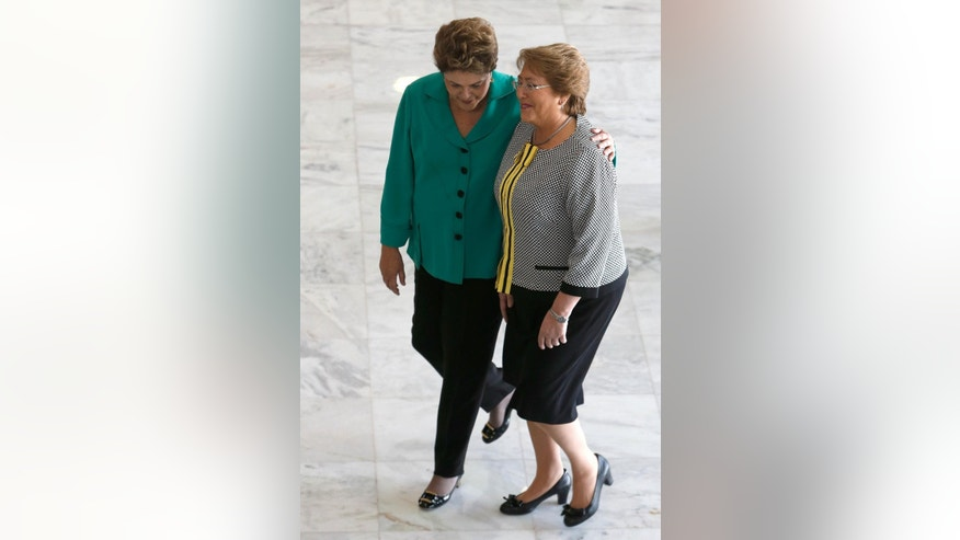 FILE - In this June 12, 2014 file photo, Brazil's President Dilma Rousseff, left, welcomes Chile's President Michelle Bachelet at Planalto presidential palace in Brasilia, Brazil. The once-popular presidents have both seen their approval ratings plunge amid corruption scandals that have battered their center-left governments, according to two polls released Wednesday, April 1, 2015. (AP Photo/Eraldo Peres, File)