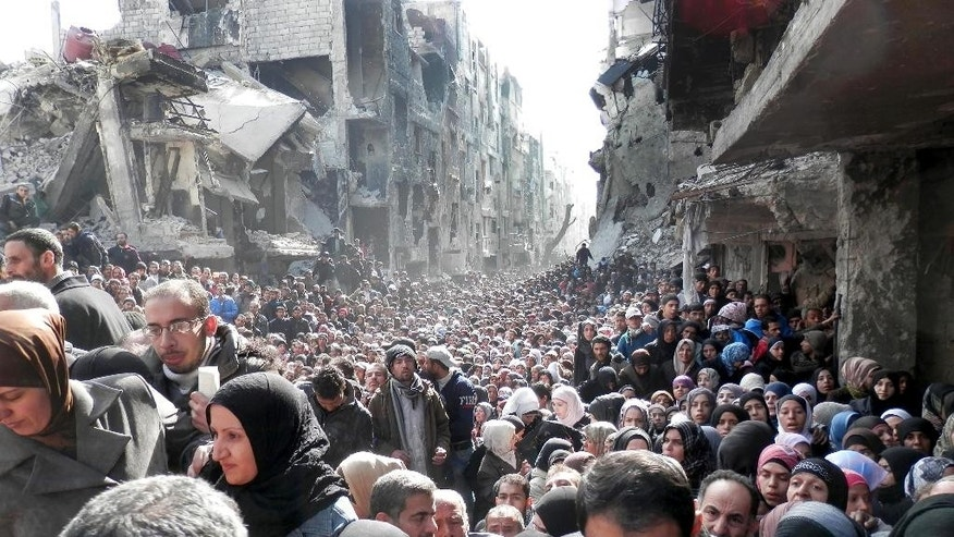 FILE - This picture taken on Jan. 31, 2014, and released by the United Nations Relief and Works Agency for Palestine Refugees (UNRWA), shows residents of the besieged Palestinian camp of Yarmouk, queuing to receive food supplies, in Damascus, Syria. On Wednesday, April. 1, 2015 Islamic State militants infiltrated the Palestinian refugee camp of Yarmouk in the Syrian capital marking the deepest foray yet by the extremist group into Damascus, seat of President Bashar Assad's power, Syrian opposition activists and Palestinian officials said. (AP Photo/UNRWA, File)