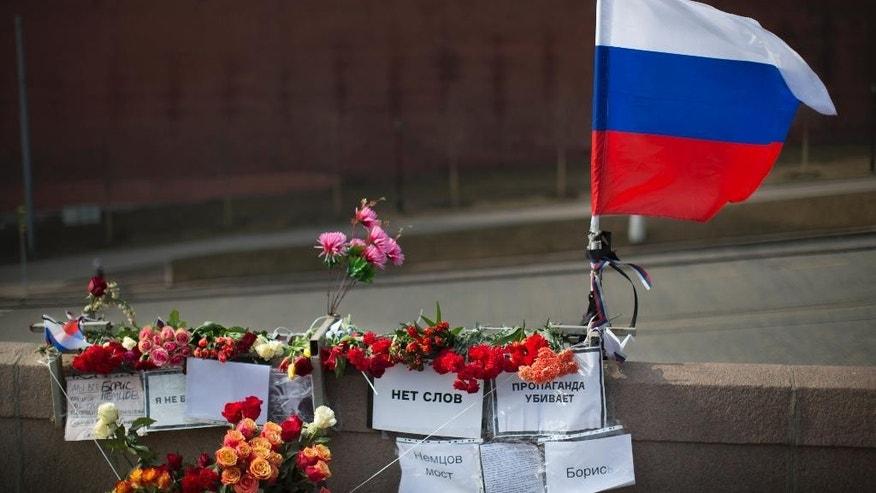 "A Russian national flag, flowers and posters reading ""No words, Propaganda kills, Boris, and Nemtsov Bridge"" are placed where Boris Nemtsov, a charismatic Russian opposition leader and sharp critic of President Vladimir Putin, was gunned down on Feb. 27, 2015 near the Kremlin in Moscow, Russia, Saturday, March 28, 2015, with the Kremlin wall is in the background. People continue to offer flowers and candles in memory of Nemtsov even after one month of his death. (AP Photo/Alexander Zemlianichenko)"