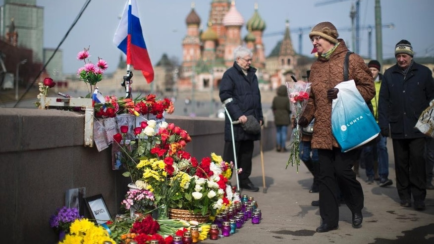 A woman lays a bunch of flowers at a place where Boris Nemtsov, a charismatic Russian opposition leader and sharp critic of President Vladimir Putin, was gunned down on Feb. 27, 2015 near the Kremlin in Moscow, Russia, Saturday, March 28, 2015. People continue to offer flowers and candles in memory of Nemtsov even after one month of his death. (AP Photo/Alexander Zemlianichenko)