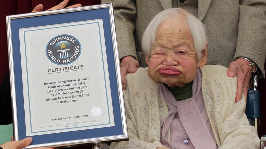Feb. 27, 2013: Japan's Misao Okawa, then 114, poses with the certificate of the world's oldest woman, which was presented to her by Guinness World Records Japan Country Manager Erika Ogawa, unseen, at a nursing home in Osaka, western Japan.