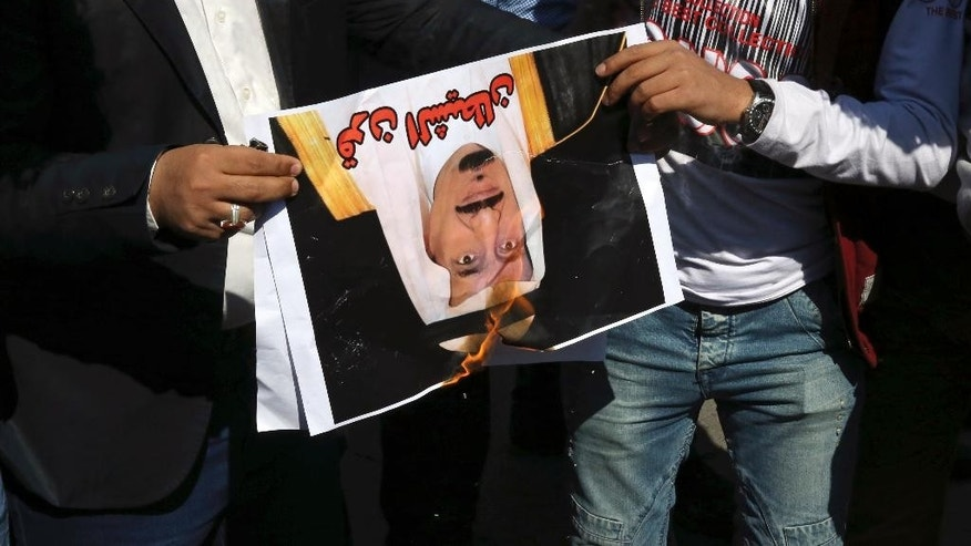 "Yemeni men hold a burning portrait of Saudi King Salman, with Arabic that reads, ""Horn of Satan,"" as scores of Yemeni expatriates, including students and clerics, protest against Saudi-led airstrikes on their homeland, in front of the Saudi Embassy, in Tehran, Iran, Wednesday, April 1, 2015. (AP Photo/Vahid Salemi)"