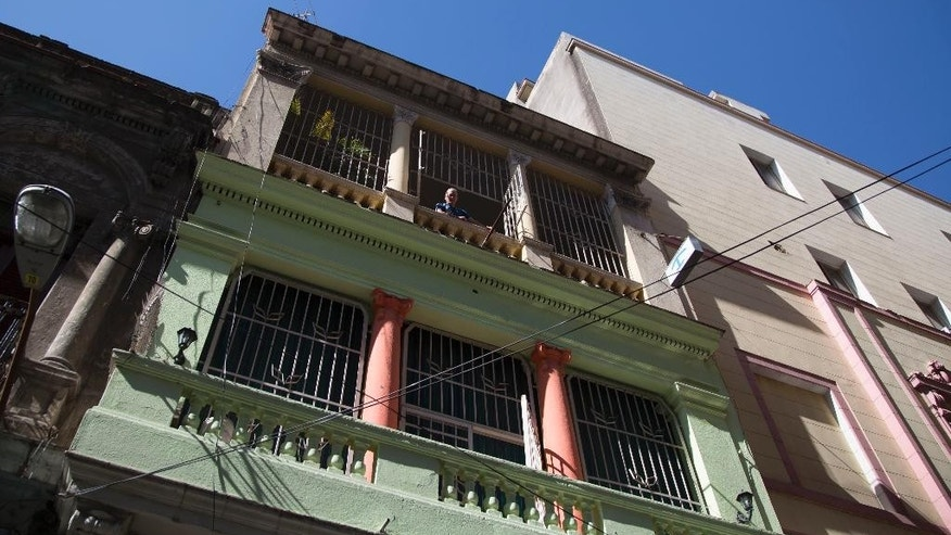 Home owner Israel Ribero looks from his home with rooms for rent in Havana, Cuba, Wednesday, April 1, 2015. The wildly popular online home-sharing service Airbnb will allow American travelers to book lodging in Cuba starting Thursday in the most significant U.S. business expansion on the island since the declaration of detente between the two countries late last year. (AP Photo/Desmond Boylan)