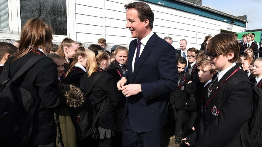 British Prime Minister David Cameron, second right, talks with pupils during a visit to the Kings Leadership Academy in Warrington, northwest England, Thursday April 2, 2015. Britain goes to the polls for a general election on Thursday May 7, 2015. (AP Photo/Leon Neal, Pool)