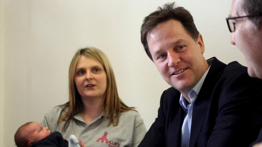 Liberal Democrat leader Nick Clegg, centre, sits with MP Mark Hunter as they meet Joanne Thompson with her six week old son Leo, during a visit to the Millie's Trust charity in Cheadle, England, Thursday April 2, 2015, as part of the election trail. Britain goes to the polls for a general election on Thursday May 7, 2015.  (AP Photo/PA,  Steve Parsons) UNITED KINGDOM OUT