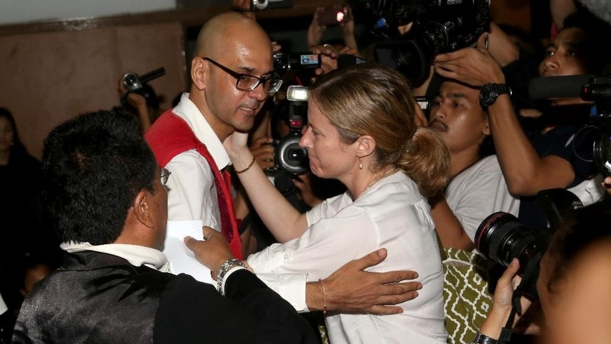 Canadian teacher Neil Bantleman, center, hugged by his wife Tracy,  after his trial at South Jakarta District Court in Jakarta, Indonesia, Thursday, April 2, 2015. An Indonesian court has sentenced Bantleman to 10 years in jail for sexually abusing three young children at a prestigious international school.(AP Photo/Tatan Syuflana)