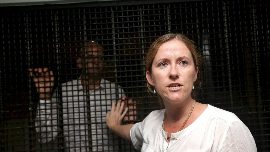 Canadian teacher Neil Bantleman, left, stands inside a holding cell while his wife Tracy talks to journalists after his trial at South Jakarta District Court in Jakarta, Indonesia, Thursday, April 2, 2015. An Indonesian court has sentenced Bantleman to 10 years in jail for sexually abusing three young children at a prestigious international school.(AP Photo/Tatan Syuflana)
