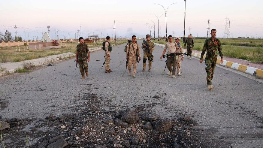"Iraqi Army (EOD) team search for bombs on the main road between Baghdad and Tikrit, 80 miles (130 kilometers) north of Baghdad, Iraq, Wednesday, April 1, 2015. Iraqi security forces battled the last remaining pockets of Islamic State militants in Tikrit on Wednesday and were expected to gain full control of the city ""within the coming hours,"" said Iraqi Interior Minister Mohammed Salem al-Ghabban. (AP Photo/Khalid Mohammed)"