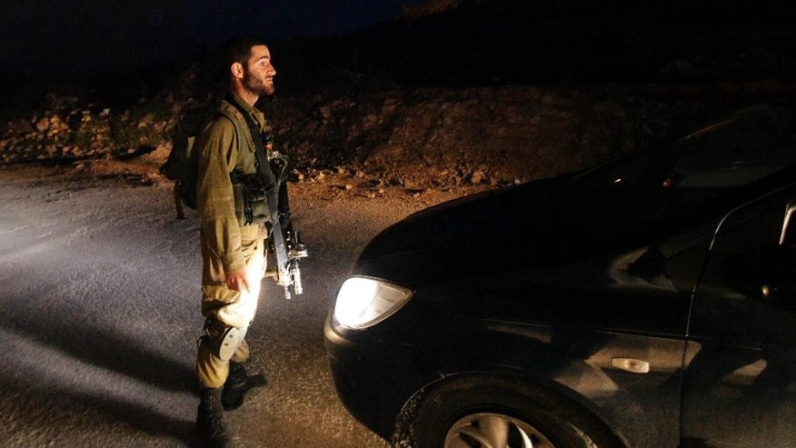 An Israeli soldier stops a car in the village of Beit Anun, West Bank, Thursday, April 2, 2015. An Israeli has gone missing in the West Bank and troops are searching for the man amid fears he could have been abducted. Last year, Palestinians abducted and killed three Israeli teenagers sparking a chain of events that led to a 50 day war in Gaza. (AP Photo/Mahmoud Illean)