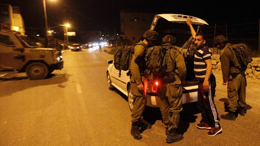 Israeli soldiers search a car in the village of Beit Anun, West Bank, Thursday, April 2, 2015. An Israeli has gone missing in the West Bank and troops are searching for the man amid fears he could have been abducted. Last year, Palestinians abducted and killed three Israeli teenagers sparking a chain of events that led to a 50 day war in Gaza. (AP Photo/Mahmoud Illean)