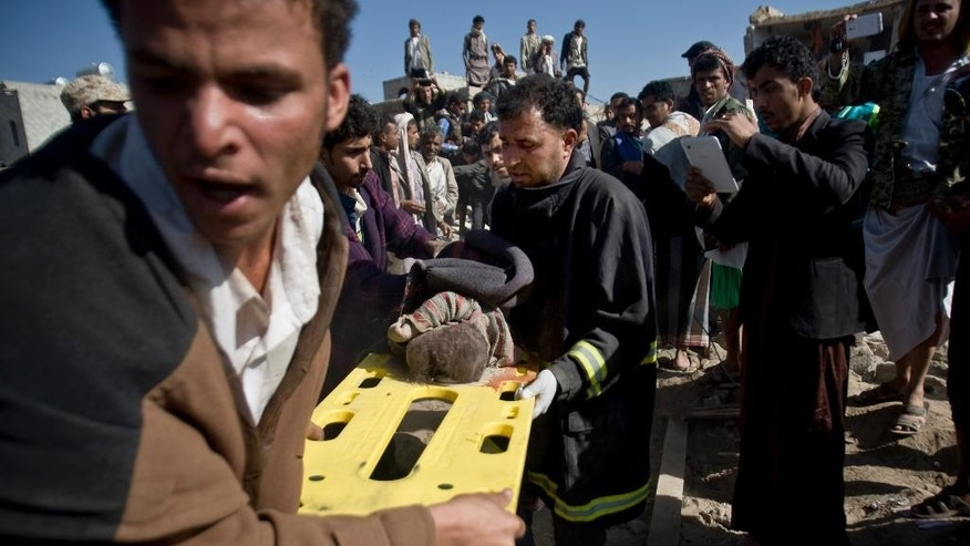 FILE - In this Thursday, March 26, 2015 file photo, people carry the body of a child they uncovered from under the rubble of houses destroyed by Saudi airstrikes near Sanaa Airport, Yemen. In just the first four days of fighting in Yemen, at least 62 children were killed by airstrikes or in clashes, UNICEF says, just one sign of the humanitarian damage being wreaked by the conflict in a country already gutted by years of chaos.(AP Photo/Hani Mohammed, File)