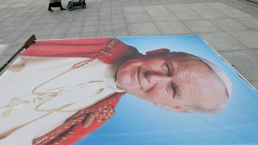 A large poster of late Pope John Paul II is laid out as Roman Catholic faithful prepare to mark the 10th anniversary of his death in Warsaw, Poland, on Thursday, April 2, 2015.(AP Photo/Czarek Sokolowski)