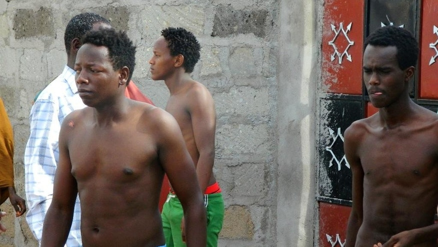 Some students without their shirts of the Garissa University College get out of a house where they seek refuge after escaping from an attack by gunmen in Garissa, Kenya, Thursday, April 2, 2015. Gunmen attacked the university early Thursday, shooting indiscriminately in campus hostels. Police and military surrounded the buildings and were trying to secure the area in eastern Kenya, police officer Musa Yego said. (AP Photo)