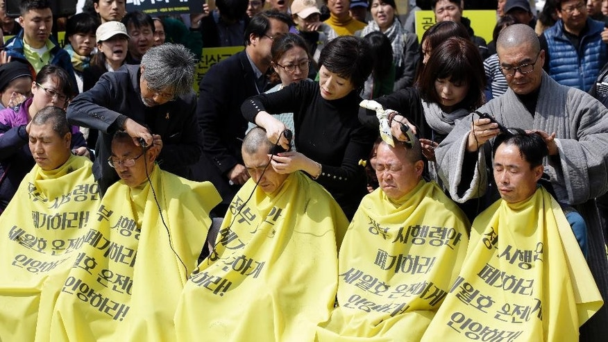 "Relatives of victims of the South Korean ferry sinking that killed more than 300 a year ago, have their heads shaved during a rally against the government's plans in Seoul, South Korea, Thursday, April 2, 2015.  Dozens of relatives of victims protested against the government plans to provide about 420 million won ($383,000) for each of the 250 students on the ship and 760 million won ($694,000) for 11 dead teachers. The letters on yellow apron read ""Intactly salvage the ferry Sewol and Abrogate the government's plan."" (AP Photo/Lee Jin-man)"