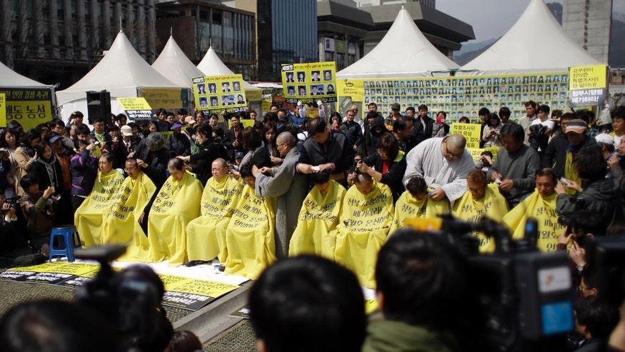 Relatives of victims of a South Korean ferry sinking that killed more than 300 a year ago, have their heads shaved during a rally against the government's plans in Seoul, South Korea, Thursday, April 2, 2015.  Dozens of relatives of the victims protested against the government plans to provide about 420 million won ($383,000) for each of the 250 students on the ship and 760 million won ($694,000) for 11 dead teachers.  (AP Photo/Lee Jin-man)