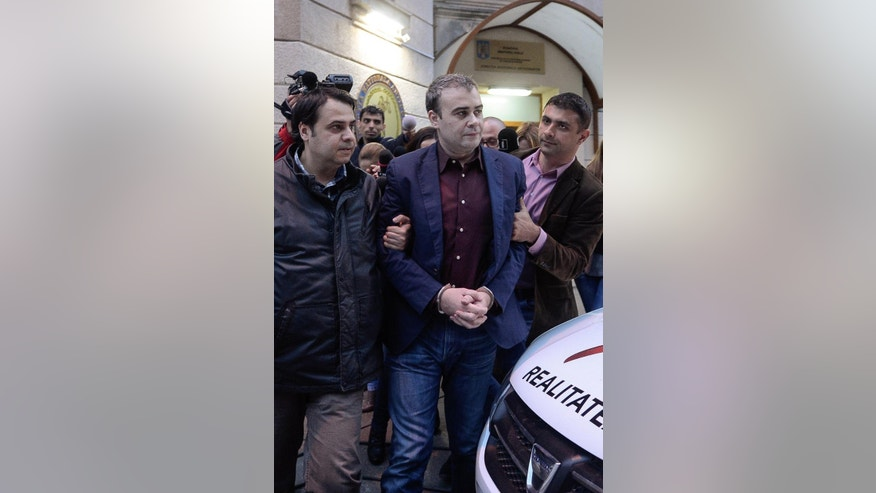 In this picture taken on Wednesday, March 25, 2015, former Romanian finance minister Darius Valcov exits handcuffed from the prosecutors office in Bucharest, Romania.   Romanian prosecutors investigating an alleged bribery scheme have questioned the former finance minister about the origins of 100 paintings, including three works by Pablo Picasso.  Prosecutors questioned Darius Valcov on Friday March 27, 2015, saying the paintings had been hidden by four of his friends. The works have been sent to art experts for evaluation. Valcov, under house arrest since Thursday, declined to comment.  (AP Photo/Octav Ganea, Mediafax) ROMANIA OUT