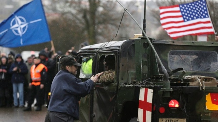 March 30, 2015: A supporter shakes hands with a US army soldier as their convoy arrives in Prague, Czech Republic. The 'Dragoon Ride' convoy started from Estonia and passed through Latvia, Lithuania and Poland before entering the Czech Republic on a return journey to a German base. (AP Photo/Petr David Josek)