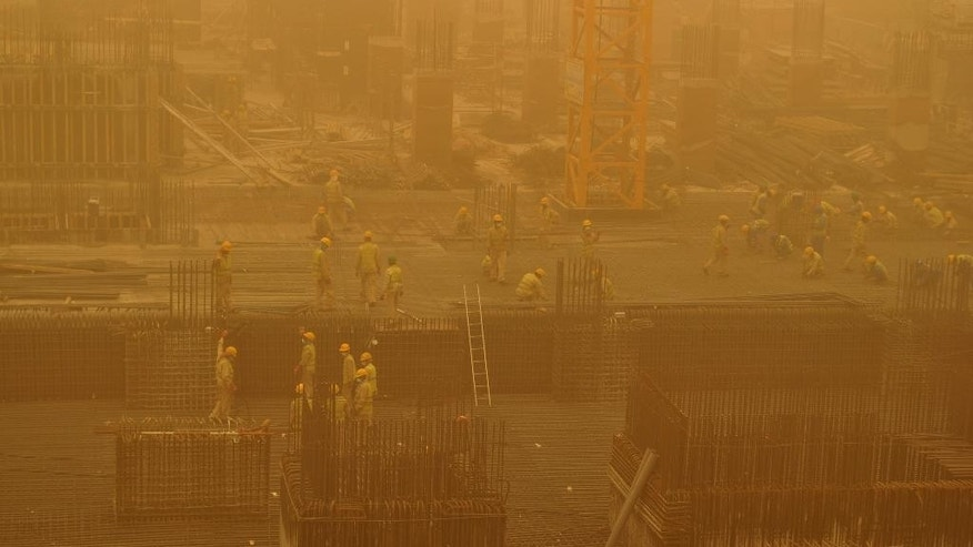 Migrant laborers, some wearing face masks, work on a construction site during a sandstorm in Dubai, United Arab Emirates, Thursday, April 2, 2015. A major sandstorm has whipped into the Mideast's commercial hub of Dubai and other Gulf cities, reducing visibility, forcing flight diversions and making breathing outside more difficult. (AP Photo/Adam Schreck)