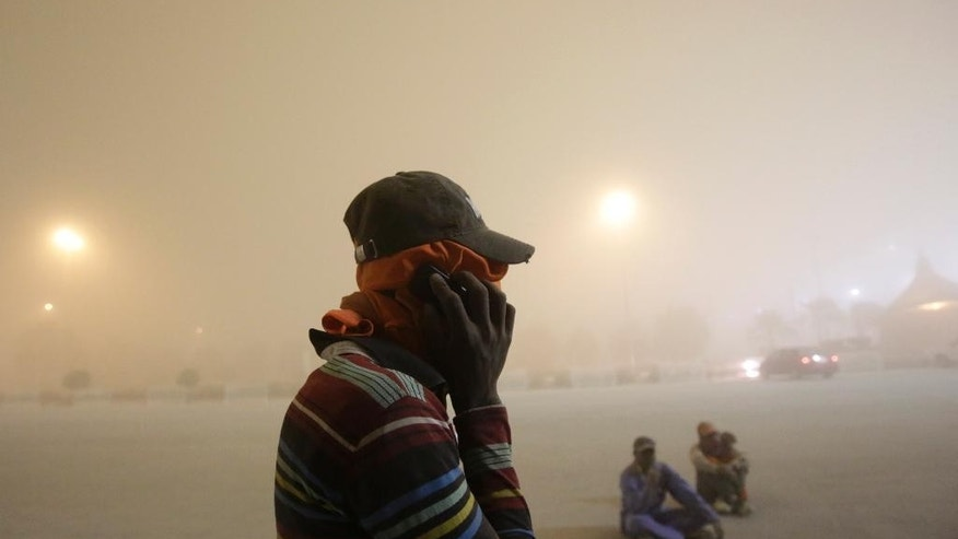 Asian laborers cover their faces from the dust as they wait for their ride just outside the Bahrain International Circuit in Sakhir, Bahrain, Wednesday, April 1, 2015. A sudden and strong sand storm hit the tiny Gulf island nation Wednesday evening. Incoming flights were suspended, the official Bahrain News Agency reported, but departures continued as of late Wednesday. (AP Photo/Hasan Jamali)