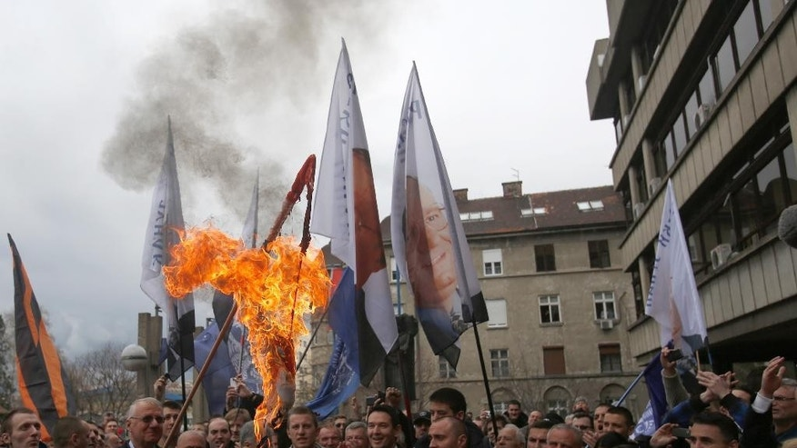 Serbian far right leader Vojislav Seselj, who is accused of war crimes by a U.N. court, burns a Croatian flag at a protest in front of the High Court in Belgrade, Serbia, Wednesday, April 1, 2015.   Serbia's Foreign Minister Ivica Dacic on Tuesday denounced a Hague Tribunal ruling that far-right leader Vojislav Seselj must return to the court's prison. (AP Photo/Darko Vojinovic)