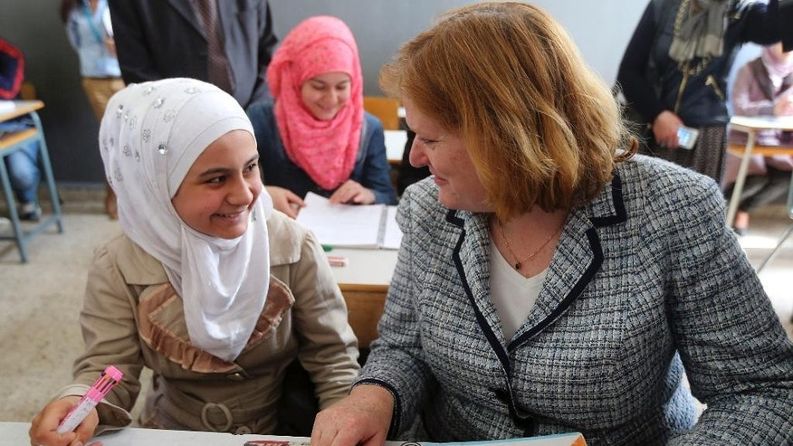 Anne Richard, assistant secretary of State of the Bureau of Population, Refugees, and Migration, right, sits with Syrian refugee students in a classroom of a Lebanese public school in Beirut, Lebanon, Thursday, April 2, 2015. Richard said Washington is planning to increase the number of Syrian refugees allowed to resettle in the United States, mostly for vulnerable cases. (AP Photo)