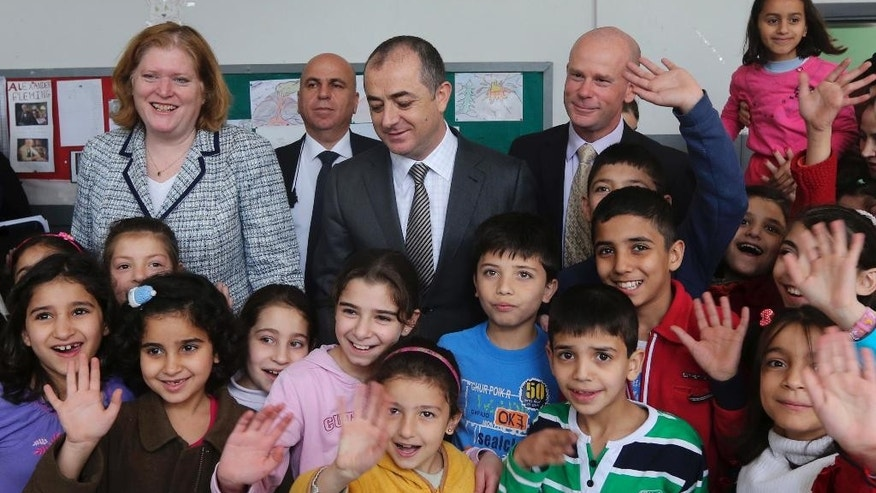 Anne Richard, assistant secretary of State of the Bureau of Population, Refugees, and Migration, left, and Lebanese Education Minister Elias Bou Saab, center, stand in a classroom among Syrian refugee students at a Lebanese public school in Beirut, Lebanon, Thursday, April 2, 2015. Richard said Washington is planning to increase the number of Syrian refugees allowed to resettle in the United States, mostly for vulnerable cases. (AP Photo)