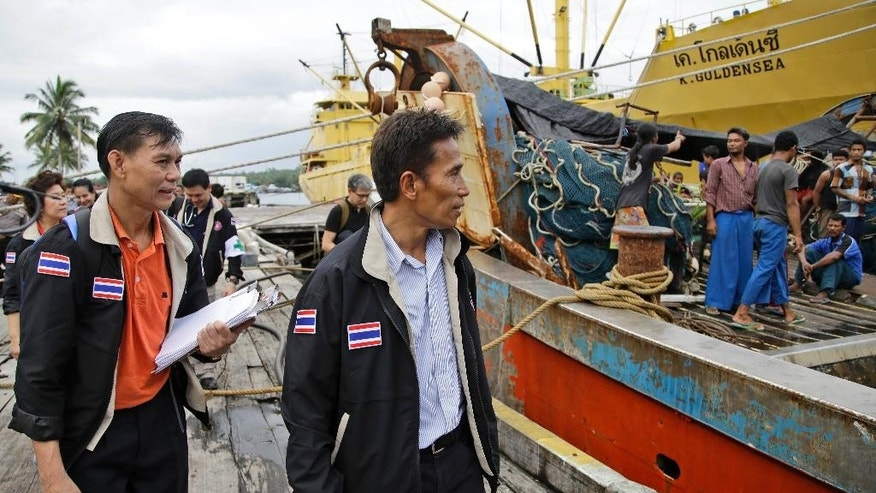 In this Wednesday, April 1, 2015 photo Thai officials inspect fishing boats docked at the compound of Pusaka Benjina Resources fishing company in Benjina, Aru Islands, Indonesia. Officials from three countries are traveling to a remote island of Indonesia to investigate how thousands of foreign fishermen wound up there as slaves and were forced to catch seafood that could eventually end up being exported to the United States and elsewhere. (AP Photo/Dita Alangkara)