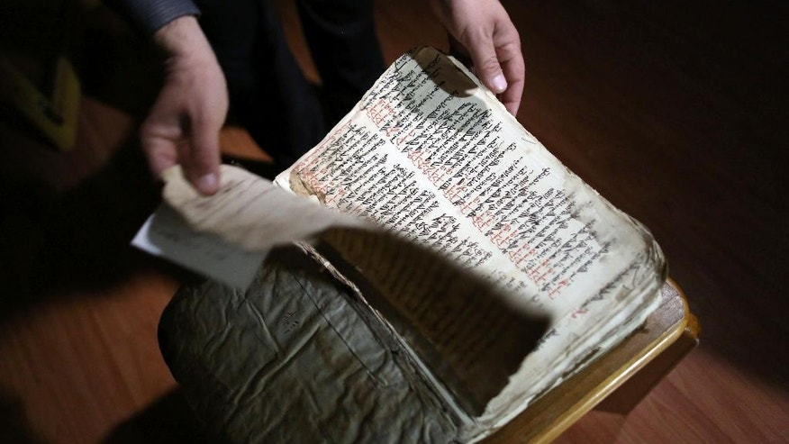 In this Thursday, April 2, 2015 photo, Raad Abdul-Ahed, 45, who was displaced from his home by the advance of Islamic State militants, shows a centuries-old handwritten biblical manuscript in the old Syriac language in a small apartment room in the Kurdish city of Dahuk, northern Iraq. As Islamic State group militants advanced toward the monastery in northern Iraq last year, the monks were determined to protect a fragile, vital piece of their heritage: They sent their library of centuries-old handwritten manuscripts to safety. Now the documents are hidden in an apartment in Iraq's Kurdish areas. (AP Photo/Bram Janssen)
