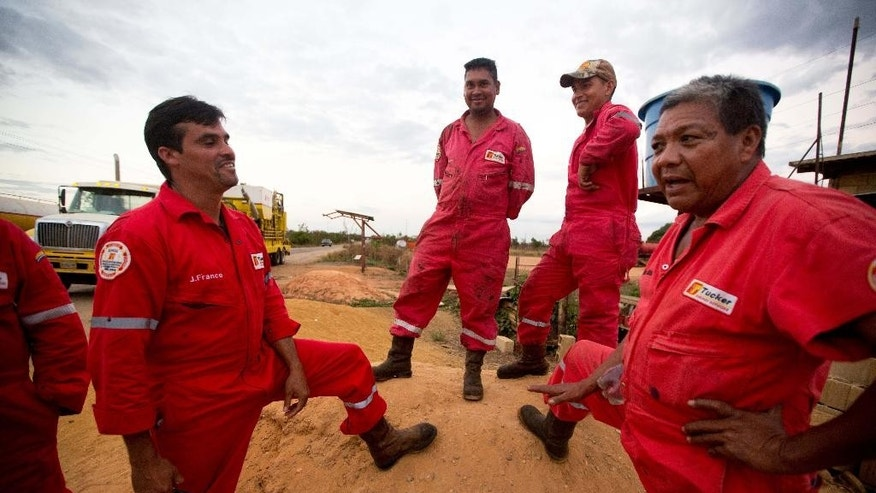In this Feb. 18, 2015 photos, oil workers from PDVSA contractor Tucker Energy Services take a break from moving equipment to an oil field near El Tigre, a town located within Venezuela's Hugo Chavez oil belt, formally known as the Orinoco Belt. The workers said their company was asking them to ready as many six new wells a week. Now it's down to half that and they fear it could drop even more. (AP Photo/Fernando Llano)