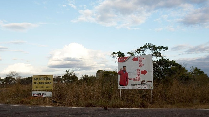 In this Feb. 18, 2015 photo, a road sign pointing to oil fields features an image of Venezuela's late President Hugo Chavez on the roadside near El Tigre, a town located within Venezuela's Hugo Chavez oil belt, formally known as the Orinoco Belt. The Costa Rica-sized area is home to the world's largest oil reserves and about half of Venezuela's current production. It's so important to the industry that Chavez traveled to this region, which was settled by American oil companies in the 1930s, when he decided to end foreign ownership of the country's oil wealth. (AP Photo/Fernando Llano)