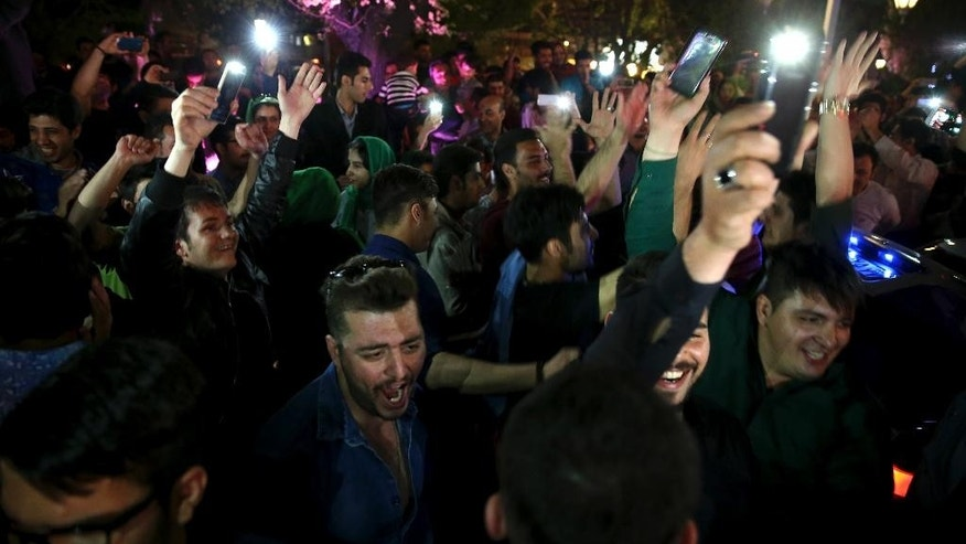 Iranians celebrate a framework agreement on Iran's nuclear program between their country and six world powers, in a street in Tehran, Iran, Friday, April 3, 2015. For the second consecutive night in Tehran, hundreds of Iranians celebrated the deal in major streets and squares. Carrying flags of Iran, singing and dancing, many chanted in support to President Hassan Rouhani and Foreign Minister Mohammad Javad Zarif. (AP Photo/Vahid Salemi)