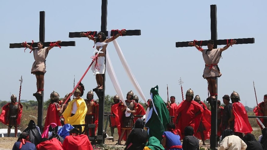 Filipino penitent Ruben Enaje, center, is nailed to the cross for the 29th time during Good Friday rituals on April 3, 2015 at Cutud, Pampanga province, northern Philippines. Several Filipino devotees had themselves nailed to crosses Friday to remember Jesus Christ's suffering and death, an annual rite frowned upon by church leaders in this predominantly Roman Catholic country. (AP Photo/Aaron Favila)