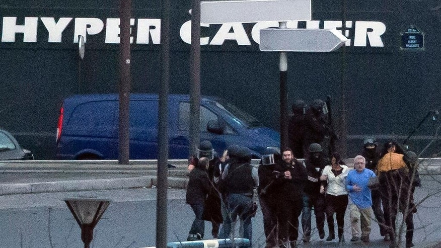 FILE - In this Jan.9, 2015 file photo, security officers escort released hostages after they stormed a kosher market to end a hostage situation, in Paris, France. Families of hostages of a radical gunman who killed four in a kosher supermarket are suing a French broadcaster over its live coverage of the attack, saying it put the hostages' lives in danger, Paris prosecutor's office spokeswoman said Friday April 3, 2015.  (AP Photo/Michel Euler, File)