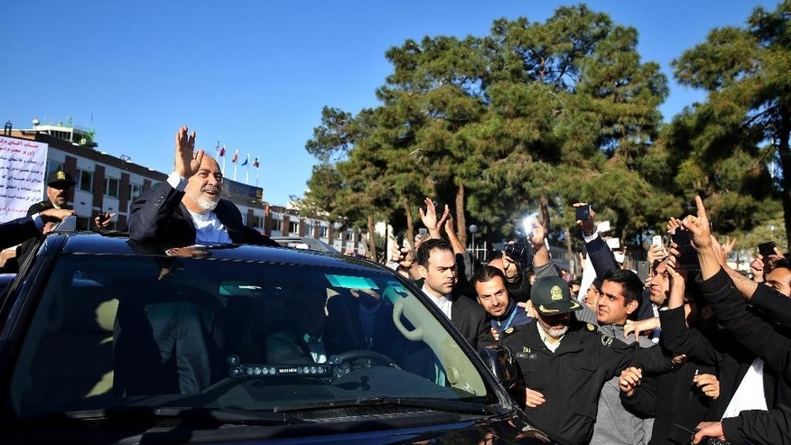 Iranian Foreign Minister Mohammad Javad Zarif, who is also Iran's top nuclear negotiator, waves to his well wishers upon arrival at the Mehrabad airport in Tehran, Iran, from Lausanne, Switzerland, Friday, April 3, 2015. Iran and six world powers reached a preliminary nuclear agreement Thursday outlining commitments by both sides as they work for a comprehensive deal aiming at curbing nuclear activities Tehran could use to make weapons and providing sanctions relief for Iran. (AP Photo/Ebrahim Noroozi)